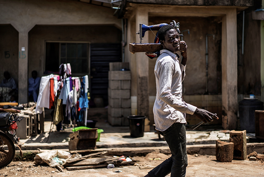 TOPSHOT - A man carries a sewing machine as he offers his tailoring services in Ojudu Berger, on June 01, 2017 / AFP PHOTO / MARCO LONGARI        (Photo credit should read MARCO LONGARI/AFP/Getty Images)
