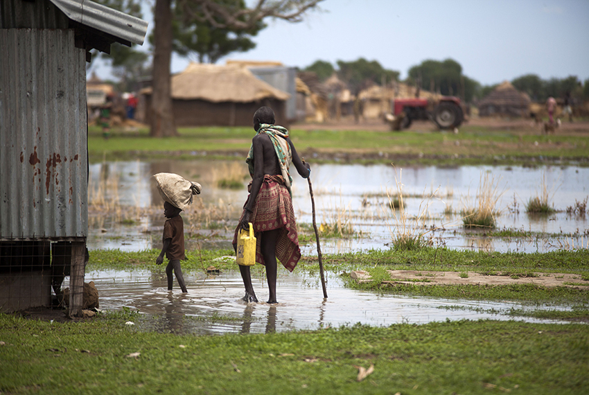 TOPSHOT - A woman with a boy walk in a flooded area on May 31, 2017, in Panthau, Northern Bahr al Ghazal, South Sudan.  The rain is a threat for many farmers in the area. An estimated 63 per cent of the population in Northern Bahr al Ghazal is experiencing severe food insecurity, according to the latest Integrated Food Security Phase Classification (IPC) report. The situation is particularly bad in Aweil West and Aweil South counties, where the exhaustion of household food stocks and growing dependence on financially inaccessible markets have left the population facing Emergency levels of food insecurity. / AFP PHOTO / Albert Gonzalez Farran        (Photo credit should read ALBERT GONZALEZ FARRAN/AFP/Getty Images)