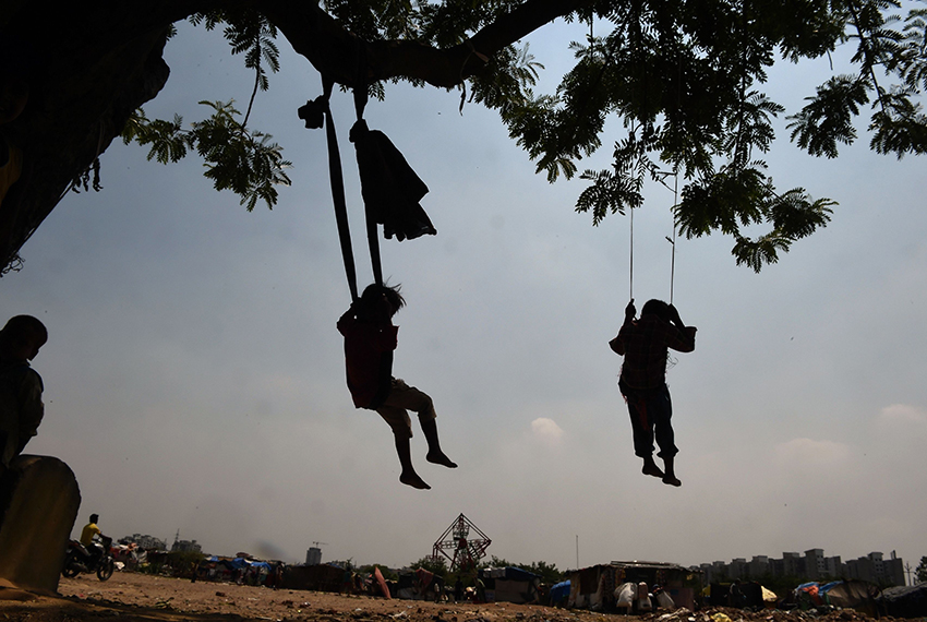 TOPSHOT - Indian children play on makeshift swings suspended from a tree on the outskirts of New Delhi on May 30, 2017. / AFP PHOTO / Prakash SINGH        (Photo credit should read PRAKASH SINGH/AFP/Getty Images)