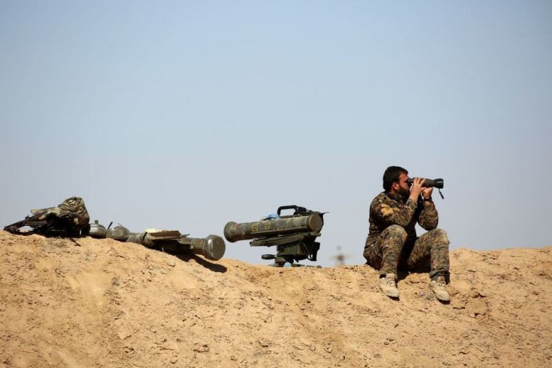 A fighter of the US-backed Syrian Democratic Forces (SDF), made up of an alliance of Arab and Kurdish fighters, looks with binoculars as he sits next to anti-tank weapons in the village of Sabah al-Khayr on the northern outskirts of Deir Ezzor as they drive to encircle the Islamic State (IS) group bastion of Raqa on February 21, 2017. The SDF made a major incursion into the oil-rich province of Deir Ezzor as part of their push for Raqa, field commander Dejwar Khabat said.      / AFP / DELIL SOULEIMAN        (Photo credit should read DELIL SOULEIMAN/AFP/Getty Images)