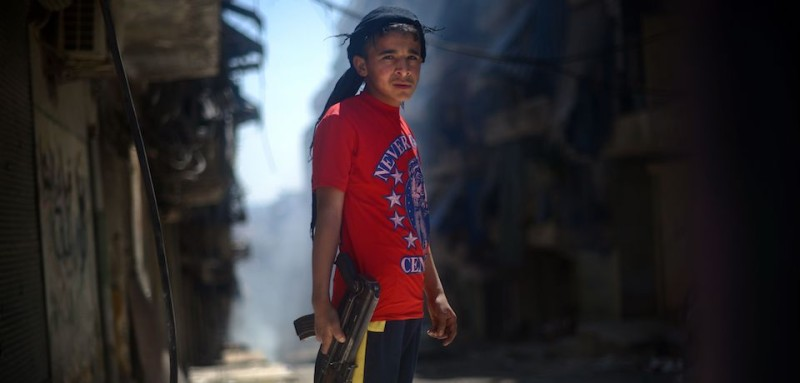 A Syrian boy holds an AK-47 assault rifle in the majority-Kurdish Sheikh Maqsud district of the northern Syrian city of Aleppo on April 14, 2013. In northern Syria, the Kurdish population has largely observed a careful compromise with regime and rebel forces, fighting alongside neither, in return for security and semi-autonomy over majority Kurdish areas, but there have been reports in recent weeks of Kurdish fighters joining the battle with Syrian rebels in certain areas, including in Sheikh Maqsud. AFP PHOTO / DIMITAR DILKOFF / AFP / DIMITAR DILKOFF        (Photo credit should read DIMITAR DILKOFF/AFP/Getty Images)