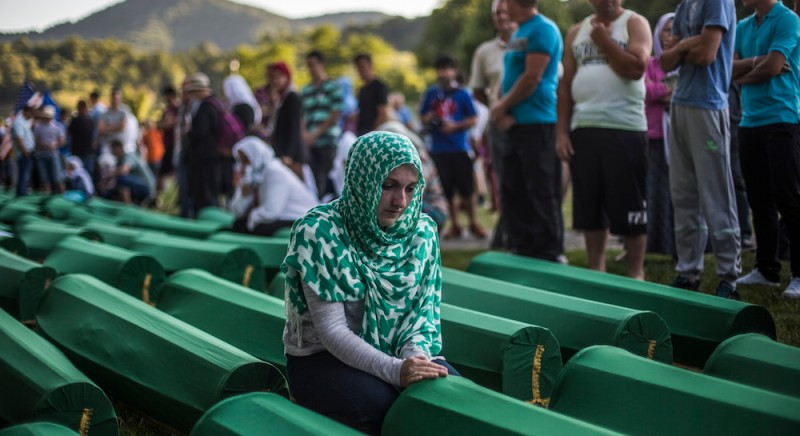 SREBRENICA, BOSNIA AND HERZEGOVINA - JULY 10:  A woman mourns over a coffin among 136 coffins of victims of the 1995 Srebrenica massacre at the Potocari cemetery and memorial near Srebrenica on July 10, 2015 in Srebrenica, Bosnia and Herzegovina. The newly-identified remains of another 136 victims from Srebrenica massacre will be buried at the ceremony on July 11, 2015 on the 20th anniversary of the massacre. At least 8,3000 Bosnian Muslim men and boys who had sought safe heaven at the U.N.-protected enclave at Srebrenica were killed by members of the Republic of Serbia (Republika Srpska) army under the leadership of General Ratko Mladic, who is currently facing charges of war crimes at The Hague, during the Bosnian war in 1995.  (Photo by Matej Divizna/Getty Images)