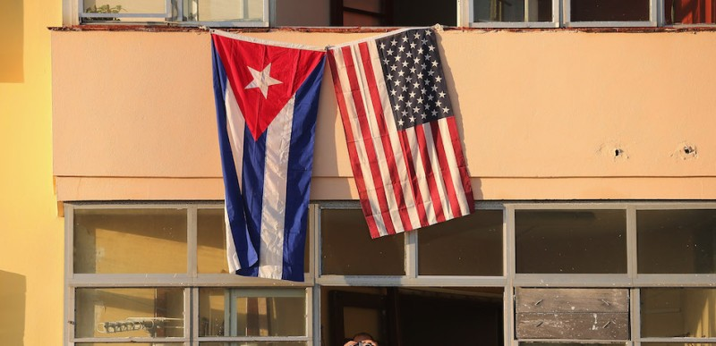HAVANA, CUBA - AUGUST 14:  Cubans look out their window across the street from the newly reopened U.S. Embassy in hopes of watching the flag-raising ceremony August 14, 2015 in Havana, Cuba. The first American secretary of state to visit Cuba since 1945, Secretary of State John Kerry visited the reopened embassy, a symbolic act after the the two former Cold War enemies reestablished diplomatic relations in July.  (Photo by Chip Somodevilla/Getty Images)