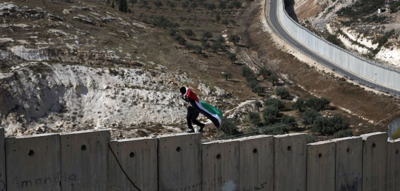 A Palestinian covered with national flag walks on top of the Israeli controvertial separation wall separating the West Bank city of Abu Dis from east Jerusalem, during clashes with Israeli security forces, on November 2, 2015. AFP HOTO / AHMAD GHARABLI        (Photo credit should read AHMAD GHARABLI/AFP/Getty Images)