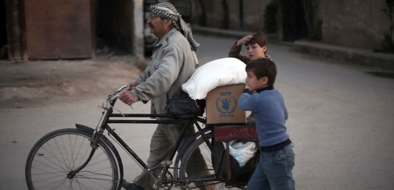 A Syrian man and his children carry sacks of wheat and aid, provided by the World Food Programme (WFP), in Kafr Batna, in the rebel-held Eastern Ghouta area, on the outskirts of the capital Damascus on March 1, 2016. Aid workers made the first delivery of desperately needed assistance since the start of Syria's fragile ceasefire, as an international task force met to try to bolster the truce. / AFP / AMER ALMOHIBANY        (Photo credit should read AMER ALMOHIBANY/AFP/Getty Images)