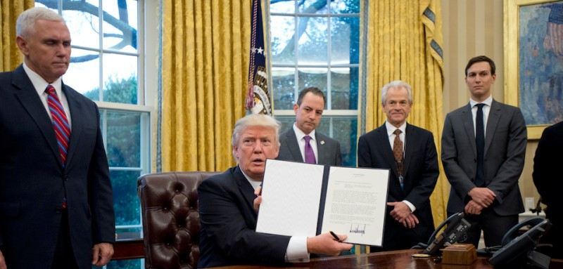 "WASHINGTON, DC - JANUARY 23:  (AFP OUT) U.S. President Donald Trump shows the Executive Order withdrawing the US from the Trans-Pacific Partnership (TPP) after signing it in the Oval Office of the White House in Washington, DC on Monday, January 23, 2017.  The other two Executive Orders concerned a US Government hiring freeze for all departments but the military, and ""Mexico City"" which bans federal funding of abortions overseas.  Standing behind the President, from left to right: US Vice President Mike Pence; White House Chief of Staff Reince Preibus; Peter Navarro, Director of the National Trade Council; and Jared Kushner, Senior Advisor to the President. (Photo by Ron Sachs - Pool/Getty Images)"