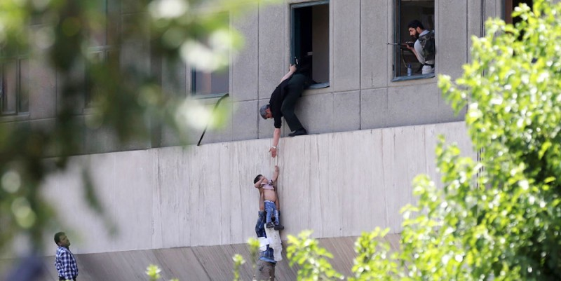 TEHRAN, IRAN - JUNE 7: A child is lowered from a window in the Iranian parliament building following an attack on June 7, 2017 in Tehran, Iran. An assault on the parliament building is now reportedly over following hours of audible gunfire. (Photo by Omid Vahabzadeh/Getty Images)