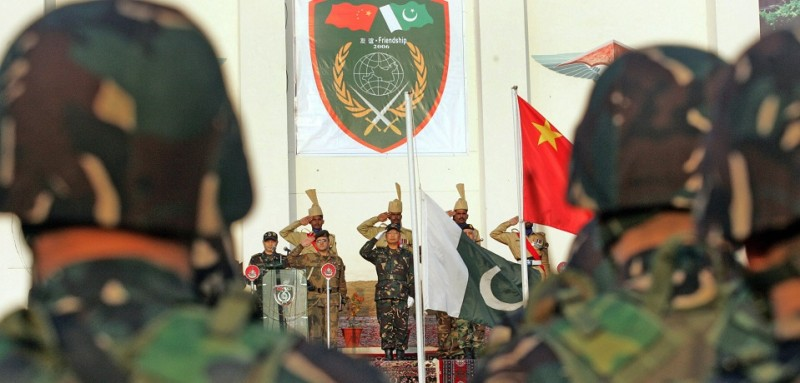 Abbottabad, PAKISTAN:  Chinese People's Liberation Army (PLA) Major General Liu Minjiang (C) and Pakistani Major General Mohsin Kamal (behind flag) stand during the opening ceremony of the ten day Pakistan-China anti-terrorist military exercise in Abbottabad, 11 December 2006.  More than 200 Chinese troops headed to Pakistan's mountainous northern region at the start of the first ever joint military exercise held here by the two allies.  AFP PHOTO/Aamir QURESHI  (Photo credit should read AAMIR QURESHI/AFP/Getty Images)