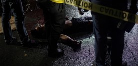 This picture taken on May 18, 2017, shows police officers investigating an alleged drug dealer killed by unidentified gunman in Manila. President Rodrigo Duterte swept to an election victory last year largely on a pledge to wipe out his nation's illegal drugs trade within three to six months, saying he would do so by killing thousands of people. Duterte fulfilled his vow on the death toll, drawing condemnation from rights groups who warned he may be orchestrating a crime against humanity as police and unknown assassins filled slums with bullet-ridden corpses. / AFP PHOTO / NOEL CELIS        (Photo credit should read NOEL CELIS/AFP/Getty Images)
