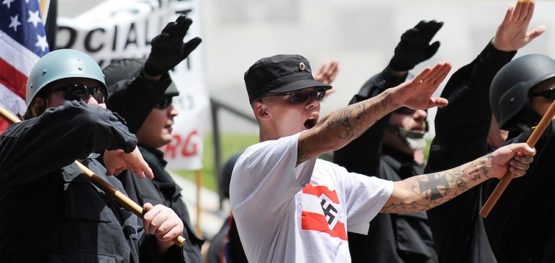 "Members of the neo-nazi group, The American National Socialist Movement, protest during a rally in front of the Los Angeles City Hall, on April 17, 2010. About 100 members of a self-described neo-Nazi group protested against immigrants to the United States on Saturday, sparking a counter-rally that drew about 500 people. The black-clad neo-Nazis were met by members of Hispanic, black and gay community groups who shouted ""Racists Go Home"" and ""Stop the Nazis."" The group, which calls itself the National Socialist Movement, requested and received a city parade permit for a white power demonstration at City Hall.   AFP PHOTO / GABRIEL BOUYS (Photo credit should read GABRIEL BOUYS/AFP/Getty Images)"