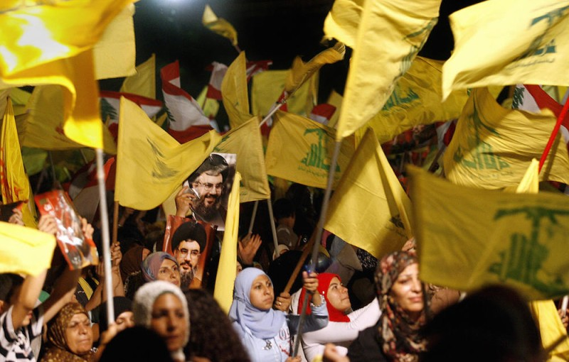 """Images of Hezbollah chief Hassan Nasrallah are seen among scores of Hezbollah and Lebanese national flags being waved by Hezbollah supporters during a ceremony to mark first anniversary of the war with Israel, 14 August 2007. Nasrallah reiterated to a mass rally broadcast live on television that his Shiite group had won a divine victory. """"Today is the anniversary of the divine victory,"""" Nasrallah told the thousands of men, women and children who had gathered in an empty lot of Beirut's southern suburb of Dahiyeh controlled by Hezbollah. AFP PHOTO/MARWAN NAAMANI (Photo credit should read MARWAN NAAMANI/AFP/Getty Images)"""