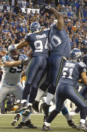 SEATTLE (AFPN) -- Defensive end (No. 94) Bryce Fisher, a captain in the Washington Air National Guard, gets airborne while trying to block a Carolina Panthers' extra-point kick during the Seattle Seahawks' 34-14 victory over the Carolina Panthers in Seattle on Jan. 22. The Seahawks clinched the National Football Conference title, are playing in Super Bowl XL on Feb. 5.(National Guard Bureau photo by Army Sgt. Jim Greenhill)