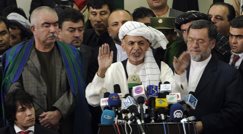 Afghan politician and former finance minister Ashraf Ghani (C) talks as his two vice-presidential candidates, former warlord Abdul Rahid Dostum (L), and former justice minister, Sarwar Danish (R), look on during registration for the forthcoming presidential elections at the Independent Election Commission (IEC) in Kabul on October 6, 2013. Afghanistan's presidential election race sparked a last-minute rush of candidates as nominations closed for next April's poll, with former finance minister Ashraf Ghani among the leading names to register. AFP PHOTO/ Massoud HOSSAINI        (Photo credit should read MASSOUD HOSSAINI/AFP/Getty Images)