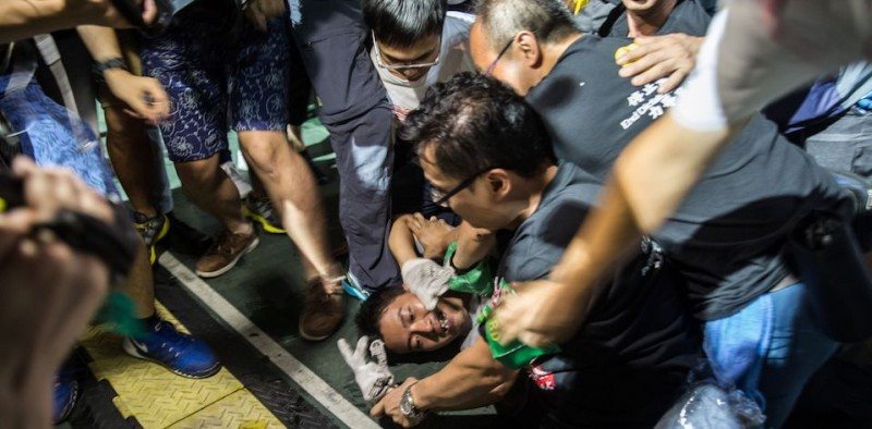 A man (bottom L) is restrained by members of security during a vigil in Hong Kong on June 4, 2016, for the commemoration of the bloody Tiananmen Square crackdown in 1989.  / AFP / ANTHONY WALLACE        (Photo credit should read ANTHONY WALLACE/AFP/Getty Images)