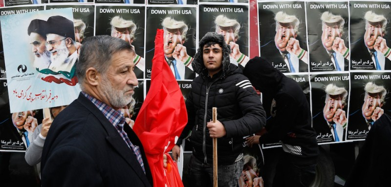 "An Iranian man stands in front of placards showing a caricature of US President Donald Trump being punched by a hand wearing a bracelet of the Iranian flag during a rally marking the anniversary of the 1979 Islamic revolution on February 10, 2017, in the capital Tehran. Millions of Iranians marched on the anniversary day in what President Hassan Rouhani described as a response to the new US administration and a rejection of ""threatening language"". / AFP / ATTA KENARE        (Photo credit should read ATTA KENARE/AFP/Getty Images)"