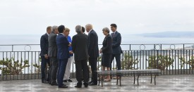 TOPSHOT - From left : President of the European Council Donald Tusk, President of the European Commission Jean-Claude Juncker, Japanese Prime Minister Shinzo Abe, German Chancellor Angela Merkel, Italian Prime Minister Paolo Gentiloni, French President Emmanuel Macron (hidden), US President Donald Trump, Britain's Prime Minister Theresa May and Canadian Prime Minister Justin Trudeau chat at the belvedere of Taormina during the Heads of State and of Government G7 summit, on May 26, 2017 in Sicily. The leaders of Britain, Canada, France, Germany, Japan, the US and Italy will be joined by representatives of the European Union and the International Monetary Fund (IMF) as well as teams from Ethiopia, Kenya, Niger, Nigeria and Tunisia during the summit from May 26 to 27, 2017. / AFP PHOTO / MANDEL NGAN        (Photo credit should read MANDEL NGAN/AFP/Getty Images)