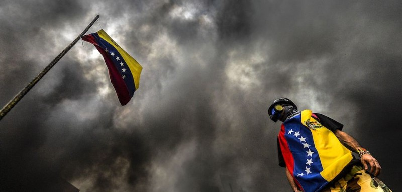 TOPSHOT - An anti-government demonstrator stands next to a national flag during an opposition protest blocking the Francisco Fajardo highway in Caracas on May 27, 2017.  Demonstrations that got underway in late March have claimed the lives of 58 people, as opposition leaders seek to ramp up pressure on Venezuela's leftist president, whose already-low popularity has cratered amid ongoing shortages of food and medicines, among other economic woes. / AFP PHOTO / LUIS ROBAYO        (Photo credit should read LUIS ROBAYO/AFP/Getty Images)