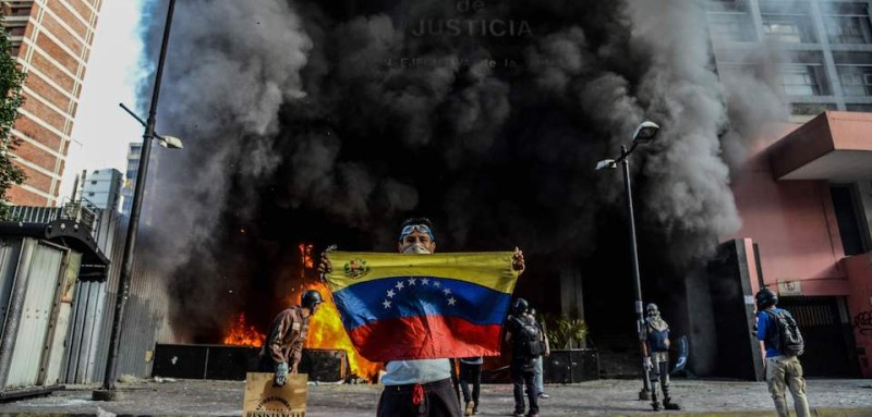 TOPSHOT - Anti-government demonstrators attack the administration headquarters of the Supreme Court of Justice as part of protests against President Nicolas Maduro in Caracas, on June 12, 2017.  With Venezuelans suffering from high inflation, food shortages and soaring crime rates, plus a deepening corruption scandal, the Venezuelan opposition has mounted near-daily anti-government protests since April 1. The protests have left 66 dead and more than a thousand injured, according to prosecutors.   / AFP PHOTO / Federico PARRA        (Photo credit should read FEDERICO PARRA/AFP/Getty Images)