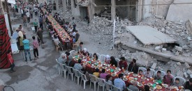 """Syrian residents of the rebel-held town of Douma, on the outskirts of the capital Damascus, break their fast with the """"iftar"""" meal on a heavily damaged street on June 18, 2017, during the Muslim holy month of Ramadan.  / AFP PHOTO / Hamza Al-Ajweh        (Photo credit should read HAMZA AL-AJWEH/AFP/Getty Images)"""