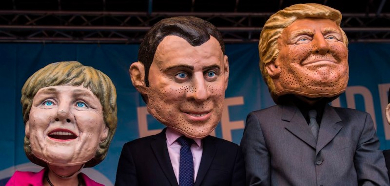 "Performers wearing masks of (L-R) German Chancellor Angela Merkel, French President Emmanuel Macron and US President Donald Trump hold a placard reading: ""Better off equal! close the gap between rich and poor"" during a demonstration called by several NGOs ahead of the G20 summit in Hamburg on July 2, 2017. / AFP PHOTO / John MACDOUGALL        (Photo credit should read JOHN MACDOUGALL/AFP/Getty Images)"