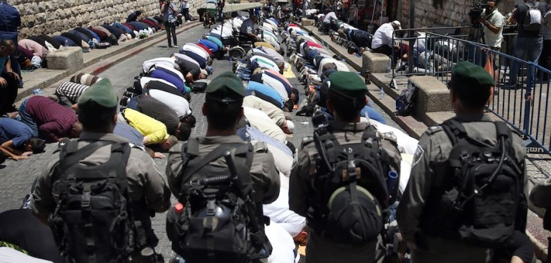 Israeli forces stand guard as Palestinian Muslim worshippers, who refuse to enter Al-Aqsa mosque compound due to newly-implemented security measures by Israeli authorities which include metal detectors and cameras, pray outside the Lions Gate, a main entrance to Al-Aqsa mosque compound, in Jerusalem's Old City on July 18, 2017. Israel reopened the ultra-sensitive holy site, after it was closed following an attack by Arab Israeli men in which two Israeli policemen were killed. / AFP PHOTO / AHMAD GHARABLI        (Photo credit should read AHMAD GHARABLI/AFP/Getty Images)