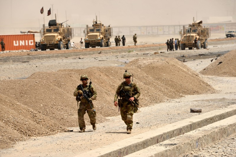 """US soldiers walk at the site of a Taliban suicide attack in Kandahar on August 2, 2017. A Taliban suicide bomber on August 2 rammed a vehicle filled with explosives into a convoy of foreign forces in Afghanistan's restive southern province of Kandahar, causing casualties, officials said. """"At around noon a car bomb targeted a convoy of foreign forces in the Daman area of Kandahar,"""" provincial police spokesman Zia Durrani told AFP.  / AFP PHOTO / JAVED TANVEER        (Photo credit should read JAVED TANVEER/AFP/Getty Images)"""