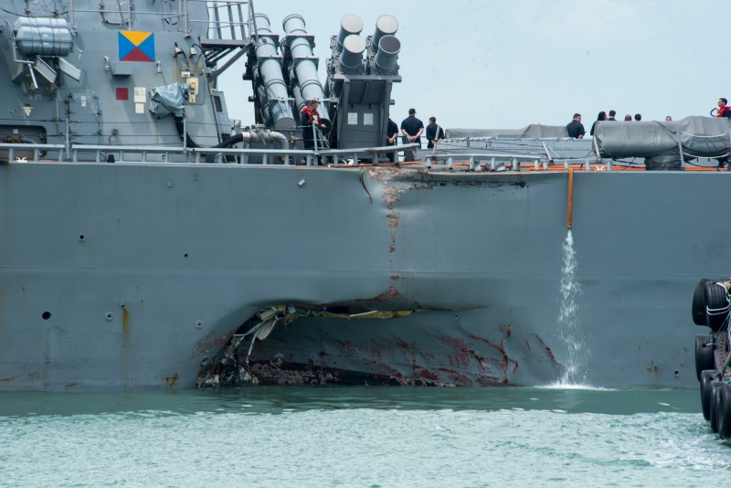 CHANGI NAVAL BASE, SINGAPORE:  In this released U.S. Navy handout, damage to the portside is visible as the Guided-missile destroyer USS John S. McCain (DDG 56) steers towards Changi Naval Base, Republic of Singapore, following a collision with the merchant vessel Alnic MC while underway east of the Straits of Malacca and Singapore on Aug. 21. Significant damage to the hull resulted in flooding to nearby compartments, including crew berthing, machinery, and communications rooms. Damage control efforts by the crew halted further flooding. The incident will be investigated. (U.S. Navy photo by Mass Communication Specialist 2nd Class Joshua Fulton/U.S. Navy via Getty Images)