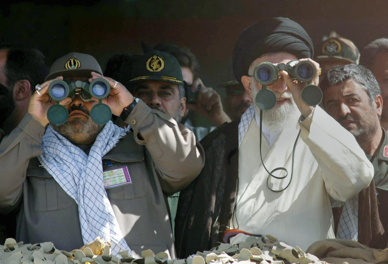 Supreme leader Ayatollah Ali Khamenei (R) and Iranian head of the military Hasan Firoz Abadi look through binoculars during the test firing of short- and medium-range missiles on 18 September 2004, amid fears in the West that Tehran is developing nuclear weapons and an ongoing review by the UN watchdog of the country's atomic energy program. AFP PHOTO/Str (Photo credit should read -/AFP/Getty Images)