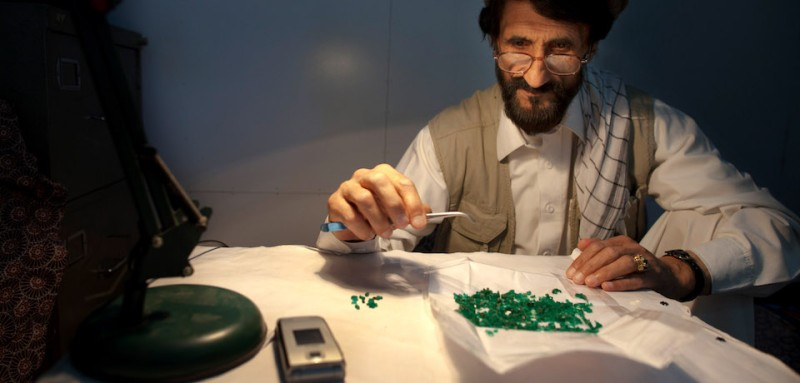 KABUL,  AFGHANISTAN - MAY 18:  Abdul examines emeralds from the Panjshir at Shams market on May 18, 2011, in Kabul, Afghanistan. The mineral resources of Afghanistan are relatively unexplored even with Afghanistan's mineral wealth of coal, copper, gold and iron ore, with precious and semiprecious stones, including high-quality emerald, lapis lazuli, red garnet and ruby. Given the country's remote and rugged terrain, on-going instability plus an inadequate infrastructure and transportation means that mining is still difficult. While many are trying to bring positive changes, Afghanistan's mining industry uses unregulated, primitive methods and outdated equipment.   (Photo by Paula Bronstein/Getty Images)
