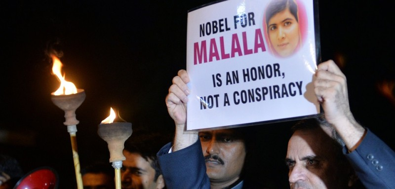 Pakistani NGO activists hold placards during an event to celebrate the award of the Nobel Peace Prize to Pakistani child education activist Malala Yousafzai in Islamabad on October 14, 2014. New Nobel peace laureate Malala Yousafzai wasted little time living up to the accolade last week, inviting the leaders of traditional foes India and Pakistan to accompany her and fellow winner Kailash Satyarthi, an Indian child rights activist, to the award ceremony. But, just hours later, a fresh exchange of fire between troops in the disputed Himalayan region of Kashmir provided a stark reminder that the prospect of lasting peace remains as distant as ever. AFP PHOTO/ Aamir QURESHI        (Photo credit should read AAMIR QURESHI/AFP/Getty Images)