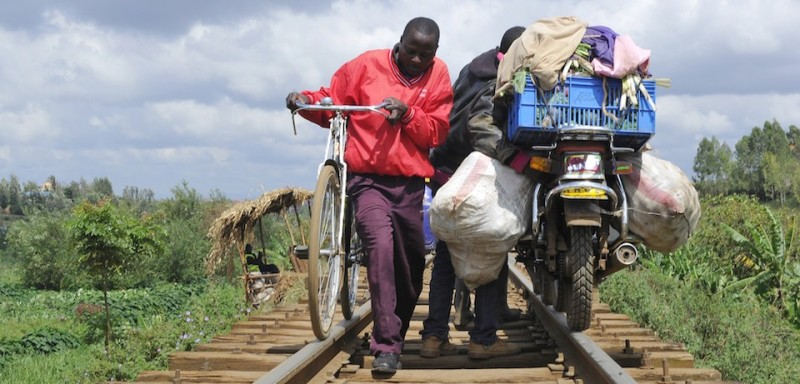 A man pushes his motorbike, and another his bike, along the tracks of a railway line on November 7, 2014 in Nairobi. Nairobi was founded in 1899 and grew up around a railway line constructed by the British colonial officials from Mombasa on the Indian Ocean coast to Uganda. The present site of Nairobi was selected as a stores depot, shunting yard and camping ground for the thousands of Indian laborers employed by the British to work on the line. AFP PHOTO/SIMON MAINA        (Photo credit should read SIMON MAINA/AFP/Getty Images)