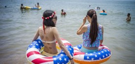 Chinese women with flotation rings adorned with colours of the US flag stand on the beach in Qingdao, eastern China's Shandong province on July 24, 2015. AFP PHOTO / FRED DUFOUR        (Photo credit should read FRED DUFOUR/AFP/Getty Images)