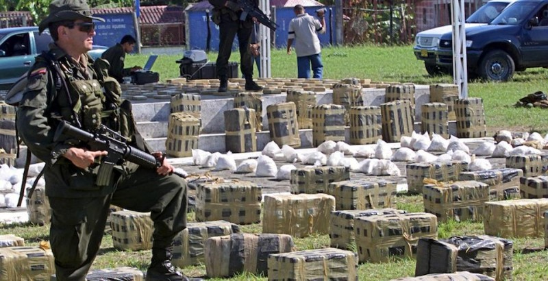TUMACO, COLOMBIA:  An anti-narcotics policeman stands guard in front of packages of cocaine that were confiscated during an operation in the port of Tumaco, in southwestern Colombia, 20 April, 2002. Three tons of cocaine, meant for shipment to the United States and Europe, were seized during the raid.  AFP PHOTO/Gerardo GOMEZ (Photo credit should read GERARDO GOMEZ/AFP/Getty Images)