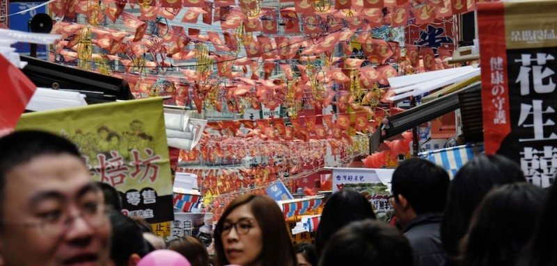 Flags with rooster patterns hang over the crowd as local residents shop in a traditional market to buy items ahead of the Lunar New Year holidays, this year marking the Year of the Rooster, in Taipei on January 19, 2017. Taiwanese decorate their homes with flowers and pray for good fortune at temples to celebrate during the annual holiday season, the biggest of the year. / AFP / SAM YEH        (Photo credit should read SAM YEH/AFP/Getty Images)