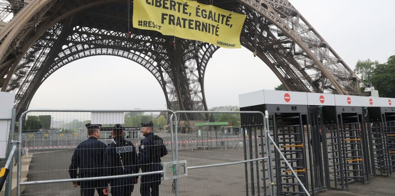 """Police officers stand by after Greenpeace activists unveiled a banner reading """"liberty, equality, fraternity"""" on the Eiffel Tower in Paris early on May 5, 2017, to protest against the far-right Front National (FN) party, two days before the second round of the presidential election. / AFP PHOTO / Jacques DEMARTHON        (Photo credit should read JACQUES DEMARTHON/AFP/Getty Images)"""