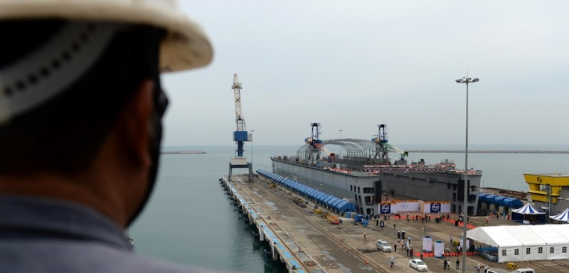 Indian workers stand alongside the FDN-2 Indian Navy floating dock as it is launched at a shipyard in Chennai on June 20, 2017. Indian-designed and constructed, the platform is capable of   docking warships of up to 8000 tons to enable repair and maintenance work. / AFP PHOTO / ARUN SANKAR        (Photo credit should read ARUN SANKAR/AFP/Getty Images)