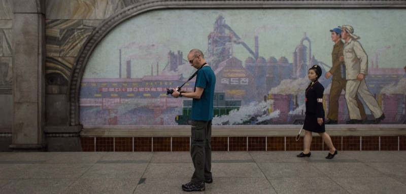 TOPSHOT - A tourist takes a photo during a visit to a subway station in Pyongyang on July 23, 2017.  The Westerners lined up before giant statues of North Koreas founder Kim Il-Sung and his son and successor Kim Jong-Il on Sunday and, on command from their guide, bowed deeply - a ritual that the Trump administration intends to stop US tourists performing, with Washington due to impose a ban on its citizens holidaying in the Democratic People's Republic of Korea (DPRK), as the North is officially known. / AFP PHOTO / Ed JONES / TO GO WITH AFP STORY NKOREA-US-TOURISM-DIPLOMACY,FOCUS BY SEBASTIEN BERGER        (Photo credit should read ED JONES/AFP/Getty Images)