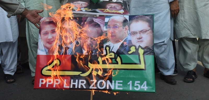 "Supporters of the Pakistan Peoples Party (PPP) burn posters bearing the image od Prime Minister Nawaz Sharif as they take part in a protest in Lahore on July 23, 2017. Pakistan's governing party has rejected as ""trash"" a corruption report accusing Prime Minister Nawaz Sharif of living beyond his means, the latest in long-running allegations which sparked calls for him to resign. The Joint Investigation Team (JIT) of civilian and military investigators has issued a report claiming there was a ""significant disparity"" in the Sharif family's income and lifestyle. / AFP PHOTO / ARIF ALI        (Photo credit should read ARIF ALI/AFP/Getty Images)"