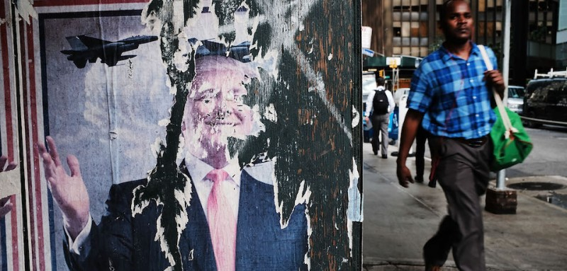 NEW YORK, NY - AUGUST 14: A man walks by a poster featuring President Donald Trump on August 14, 2017 in New York City. Security throughout the Manhattan is high today as President Trump is expected to arrive at his residency at Trump Tower later today, his first visit back to his apartment since the inauguration. Numerous protests and extensive road closures are planned for the area.  (Photo by Spencer Platt/Getty Images)