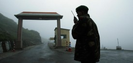 """To go with India-China-military-diplomacy,FOCUS by Pratap Chakravarty  (FILES) In this file photograph taken on July 4, 2006, an Indian soldier communicates with colleagues on a walkie talkie at Nathula Gate, leading to the Nathu La border crossing between India and China, some 50 kms (31 miles) east of Sikkim state capital Gangtok.  A recent Chinese think-tank suggestion that India should be broken up into smaller states has touched a raw nerve in India and highlighted the prickly relations between the giant neighbours. Fears of India's vulnerability were heightened by naval chief Sureesh Mehta admitting on August 10, 2009 that India could not compete with China on defense spending and warned Beijing was """"creating formidable military capabilities."""" AFP PHOTO/FILES/Deshakalyan CHOWDHURY (Photo credit should read DESHAKALYAN CHOWDHURY/AFP/Getty Images)"""