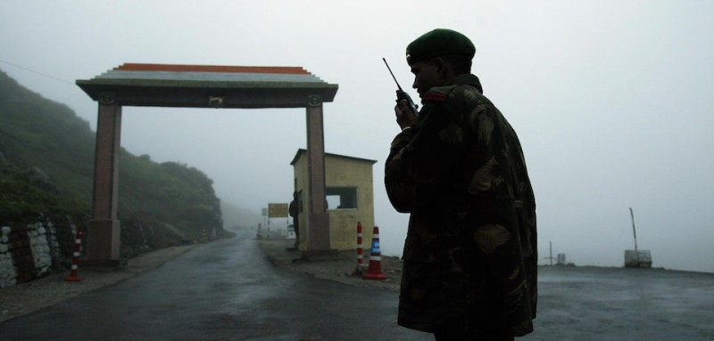 "To go with India-China-military-diplomacy,FOCUS by Pratap Chakravarty  (FILES) In this file photograph taken on July 4, 2006, an Indian soldier communicates with colleagues on a walkie talkie at Nathula Gate, leading to the Nathu La border crossing between India and China, some 50 kms (31 miles) east of Sikkim state capital Gangtok.  A recent Chinese think-tank suggestion that India should be broken up into smaller states has touched a raw nerve in India and highlighted the prickly relations between the giant neighbours. Fears of India's vulnerability were heightened by naval chief Sureesh Mehta admitting on August 10, 2009 that India could not compete with China on defense spending and warned Beijing was ""creating formidable military capabilities."" AFP PHOTO/FILES/Deshakalyan CHOWDHURY (Photo credit should read DESHAKALYAN CHOWDHURY/AFP/Getty Images)"