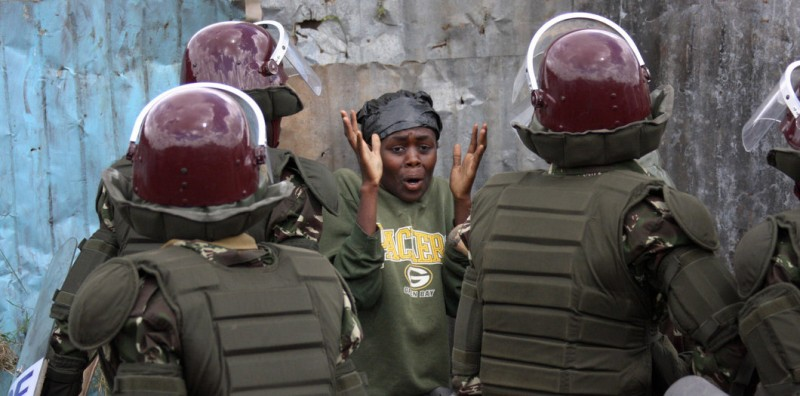 A woman is surrounded by riot police during disturbances in the Dandora district of Nairobi 14 April, 2008.  At least 14 people were killed  in Kenya when police clashed with members of a banned sect who went on the rampage and burned many vehicles after the murder of the wife of their jailed leader. Police said five people were killed in Nairobi, five in the Rift Valley and  four in central Kenya regions, where members of the outlawed Mungiki sect were blocking roads and stoning motorists.     AFP PHOTO / Stringer (Photo credit should read STRINGER/AFP/Getty Images)
