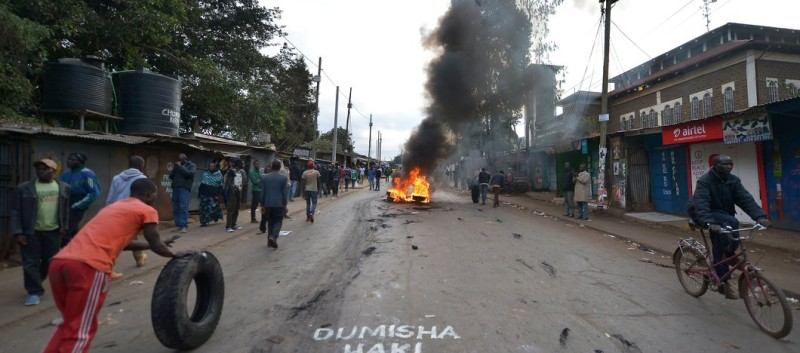 A protesting resident pushes a tyre  - past a sign on the road calling for peace in Swahili -  to add to a burning barricade on a road in Kibera Slum in Nairobi on August 9, 2017, as he takes part with others in protests in the Raila Odinga-led opposition alliance National Super Alliance (NASA) stronhhold in the Kenyan capital following the announcement of national election results.  Police engaged in running battles with a few hundred protesters in Odinga's bastion Kisumu in western Kenya, firing tear gas as his supporters set tyres alight as burning barricades also went up in Nairobi's Mathare slum as ballots from 94 percent of polling stations counted showed Kenyatta leading with 54.4 percent of the over 14 million ballots tallied against Odinga's 44.7 percent.  / AFP PHOTO / TONY KARUMBA        (Photo credit should read TONY KARUMBA/AFP/Getty Images)