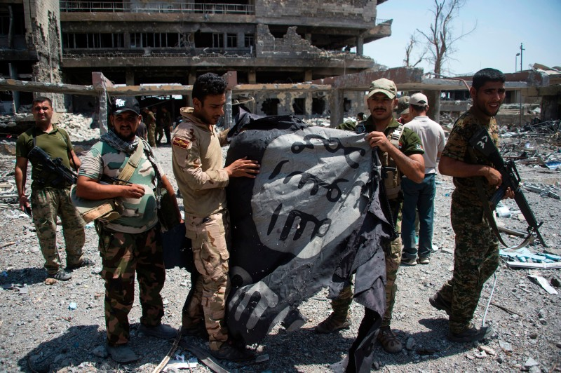 Members of Iraq's elite Rapid Response Division hold upside-down the black flag of the Islamic State (IS) group as they patrol in the Shifa neighbourhood, on the west bank of Mosul, on July 1, 2017, where they are battling some of the last members of the Islamic State (IS) jihadist group in the city. / AFP PHOTO / Fadel SENNA        (Photo credit should read FADEL SENNA/AFP/Getty Images)