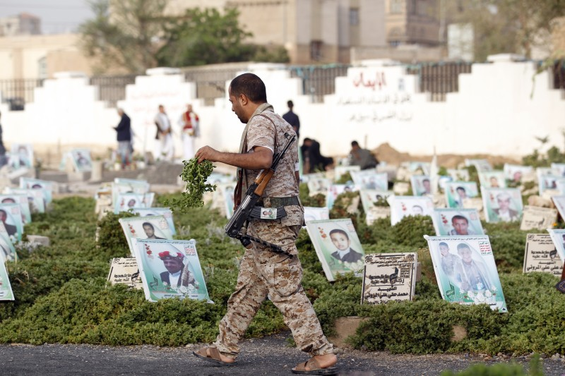 A Yemeni man carrying a gun walks past graves in a cemetery in the capital Sana on June 25, 2017 after the Eid al-Fitr prayer, which marks the end of the holy month of Ramadan. / AFP PHOTO / Mohammed HUWAIS        (Photo credit should read MOHAMMED HUWAIS/AFP/Getty Images)