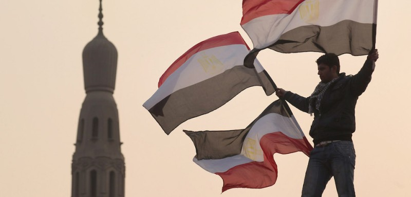 CAIRO, EGYPT - FEBRUARY 01:  A youth waves Egyptian flags from a lamp post in Tahrir Square on February 1, 2011 in Cairo, Egypt. The Egyptian army has said it will not fire on protestors as they gather in large numbers in central Cairo.  (Photo by Peter Macdiarmid/Getty Images)