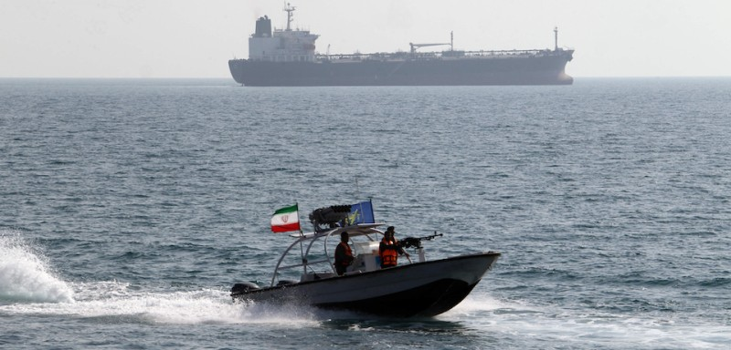 Iranian Revolutionary Guards drive a speedboat in front of an oil tanker during a ceremony to commemorate the 24th anniversary of the downing of Iran Air flight 655 by the US navy, at the port of Bandar Abbas on July 2, 2012. The plane was shot down by mistake over the Gulf by the US navy's guided missile cruiser, USS Vincennes, during confrontation with Iranian speedboats on July 3, 1988, killing 290 civilian passengers and crew members. AFP PHOTO/ATTA KENARE        (Photo credit should read ATTA KENARE/AFP/GettyImages)