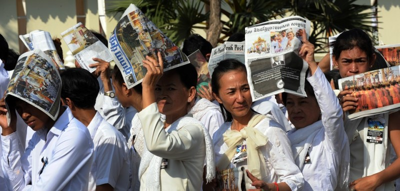 Cambodian people cover their heads with local newspapers as they wait to pray for the late former King Norodom Sihanouk at the cremation site near the Royal Palace in Phnom Penh on February 2, 2013.  A sea of mourners filled the streets of the Cambodian capital on February 1, for a lavish funeral for revered former king Norodom Sihanouk, who towered over six tumultuous decades in his nation's history.  AFP PHOTO/TANG CHHIN SOTHY        (Photo credit should read TANG CHHIN SOTHY/AFP/Getty Images)