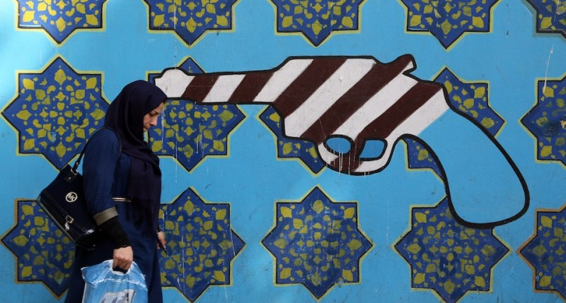 "An Iranian woman walks past a mural depicting a revolver bearing the colours of the US national flag and spread on the wall of the former US embassy in Tehran, on September 2, 2015, during the inauguration ceremony of a memorial plaque bearing one hundred anti-American comments made by the Islamic republic's late founder Ayatollah Ruhollah Khomeini outside the embassy. The leader of the Islamic revolution dubbed the United States the ""Great Satan"" on account of its policies and support for Shah Mohammad Reza Pahlavi, the last royal ruler before the Islamic republic was founded. AFP PHOTO / ATTA KENARE        (Photo credit should read ATTA KENARE/AFP/Getty Images)"