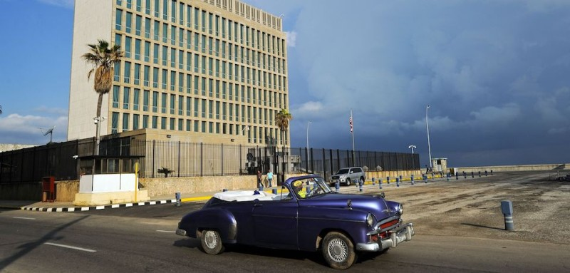 "TOPSHOT - An old American car passes by the US Embassy in Havana on December 17, 2015. The United States announced Thursday the resumption of regular flights to and from Cuba, the latest step in a historic thaw in relations. ""On December 16, the United States and Cuba reached a bilateral arrangement to establish scheduled air services between the two countries,"" the State Department said in a statement. / AFP / YAMIL LAGE        (Photo credit should read YAMIL LAGE/AFP/Getty Images)"
